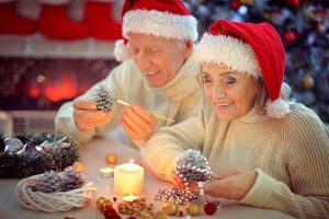 65629480 - portrait of smiling senior couple in santa hats preparing for christmas in the evening